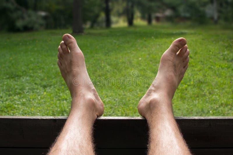 Barefoot man relaxing and enjoying a green grass garden royalty free stock photography