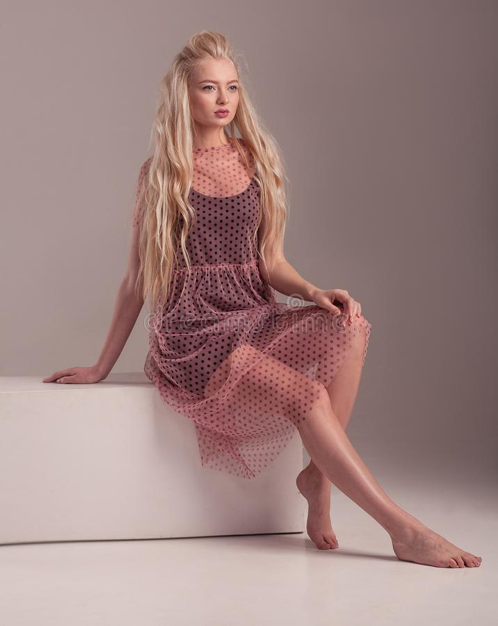 Barefoot model in dress posing on pink background. stock photo