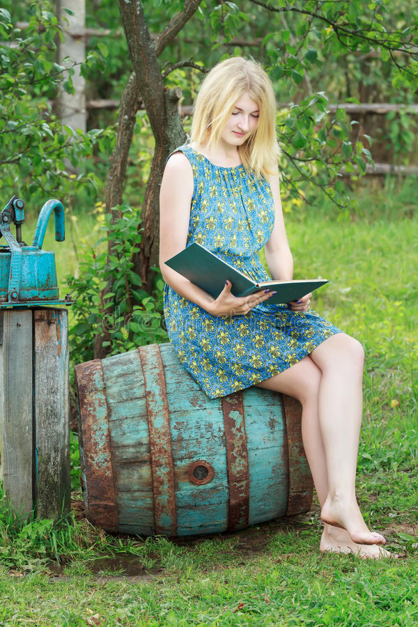 Barefoot Student Girl In Garden Is Reading Book With Blue Cover ...
