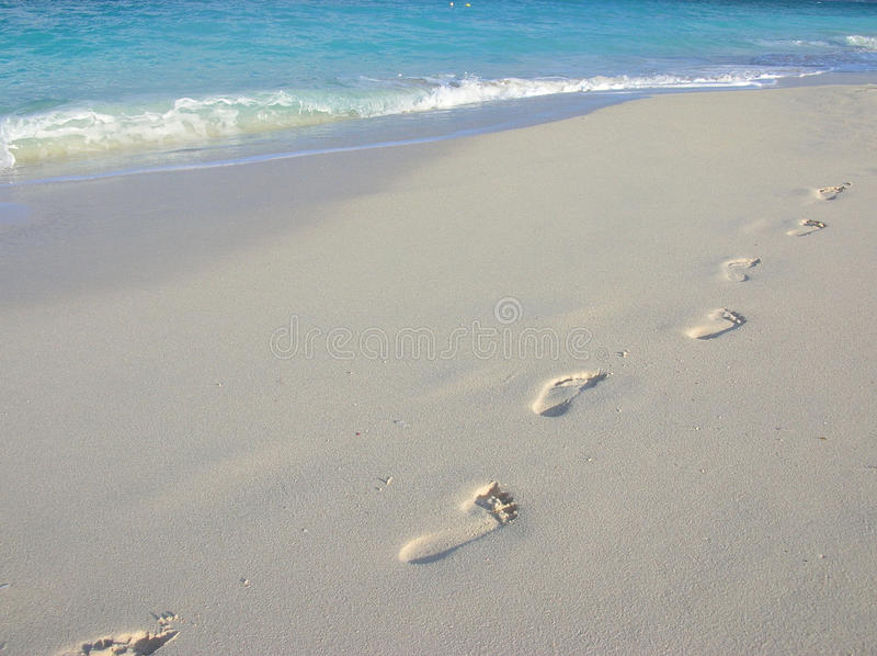 Barefoot trekking. Footprints on 7 Mile Beach, Grand Cayman stock image