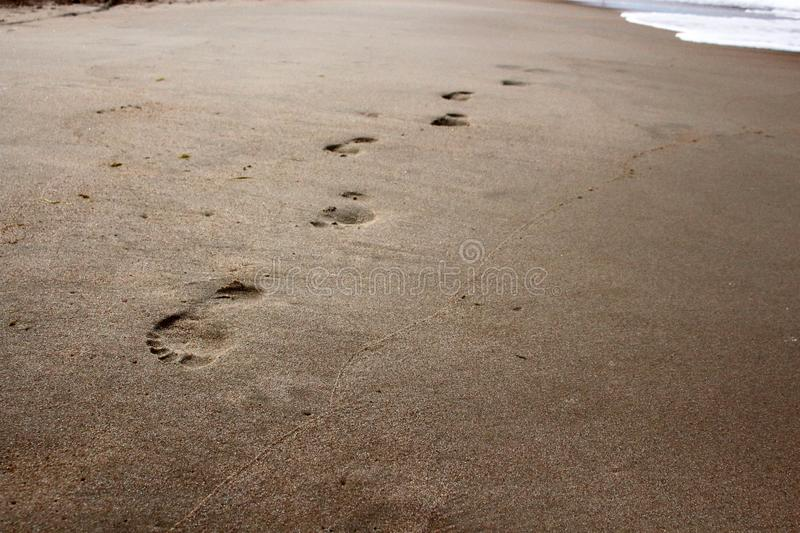 Barefoot walking footprints in the beach sand near the sea wave royalty free stock photos