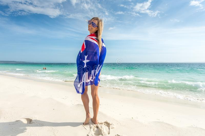 Smiling woman with Australian flag wrapped around her body sunny stock photo