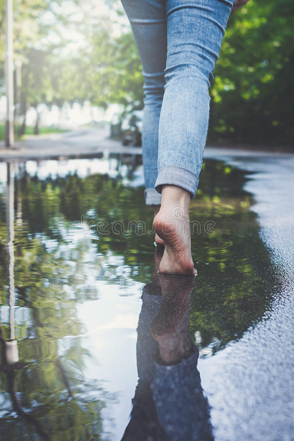 Barefoot woman in blue jeans walking through puddle of water royalty free stock images