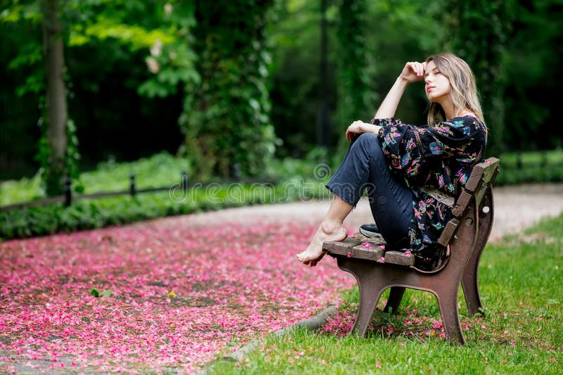 Barefoot woman is sitting on a bench at alley with blossom trees stock photography