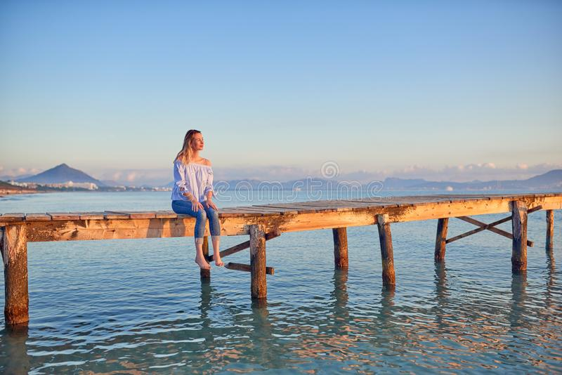 Barefoot woman sitting on a rustic wooden coastal pier royalty free stock images