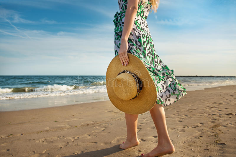Barefoot woman walking on the ocean beach sand and enjoy the vacation during the tourist trip to the tropical island stock photo