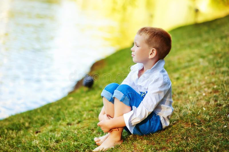 Barefoot 5 years old boy sit on lake shore and look away. Child in white shirt and blue jeans without shoes near water close to royalty free stock images
