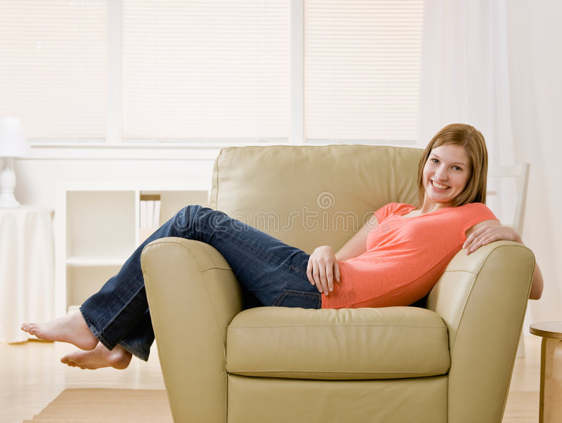 Barefoot young woman lounging on armchair at home. Casual barefoot young woman lounging on armchair at home royalty free stock image