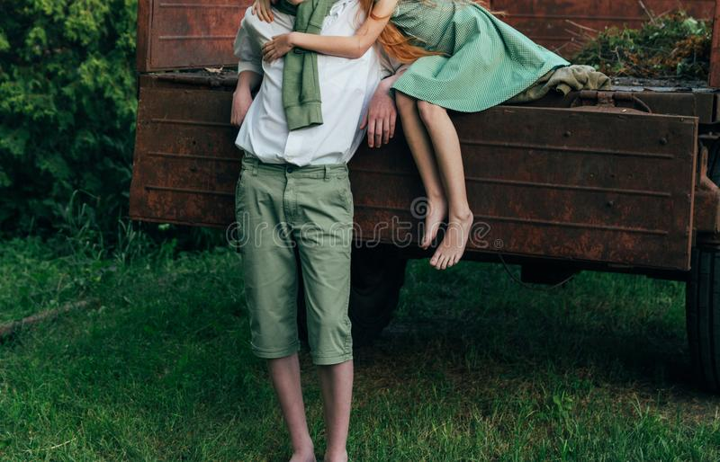 A barefooted girl in a green dress sits on the back of a car and hugs a barefoot, next to a standing guy, a summer day in the vill stock photography