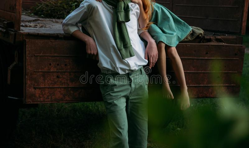 A barefooted girl in a green dress sits on the back of a car and hugs a barefoot, next to a standing guy, a summer day in the vill. A barefooted girl in a green stock photo