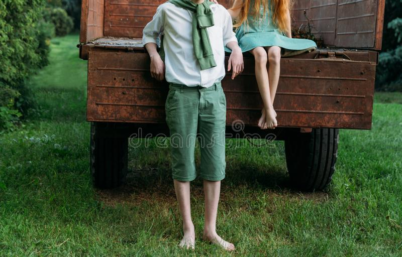 A barefooted girl in a green dress is sitting in an old caravan, and beside her, barefoot, on the grass, stands a guy in a white s. Hirt and green pants, with a stock photography