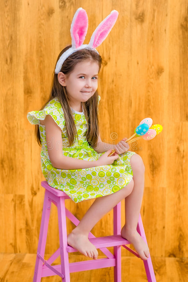 Barefooted girl wearing pink white rabbit or bunny ears and holding bunch of colorful eggs stock photo