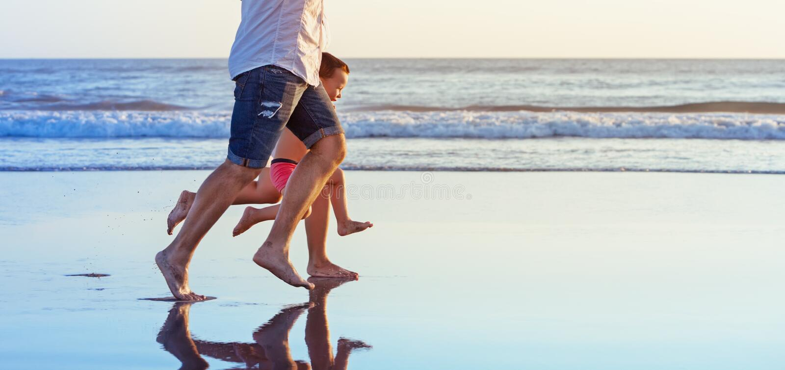 Barefooted legs of family running on beach stock image