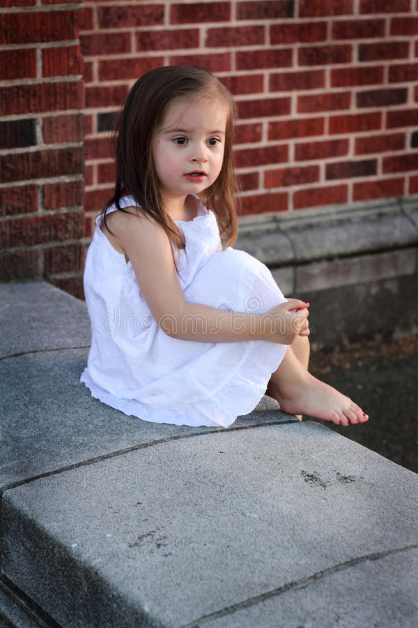 Barefooted Little Girl in White. A closeup of a barefooted little girl in a white summer dress sitting by a brick wall. Shallow depth of field stock photography