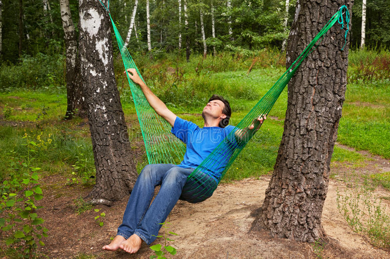 Barefooted man sits in hammock royalty free stock photography