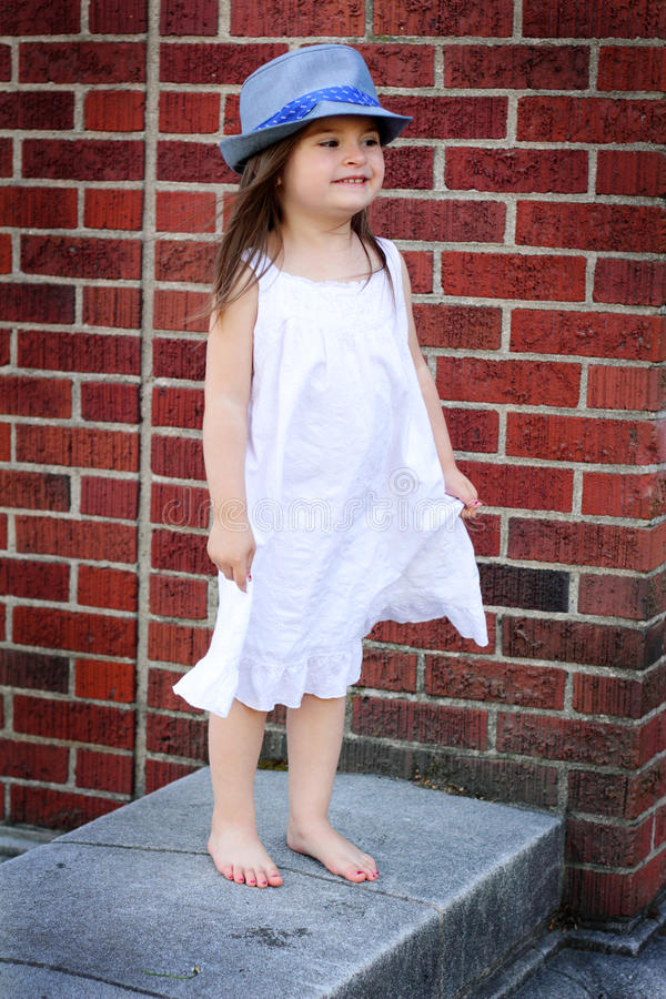 Barefooted in Silly Hat. A closeup of a barefooted little girl in a white summer dress standing on a concrete wall wearing a silly hat. Shallow depth of field stock photography