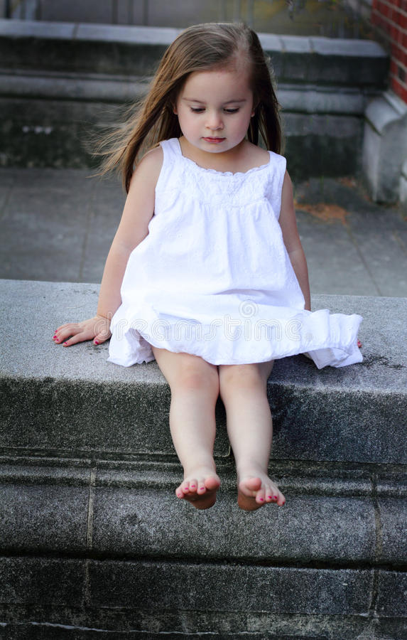 Barefooted Toddler in White. A closeup of a barefooted little girl in a white summer dress sitting on a concrete wall and looking down. Shallow depth of field stock photo