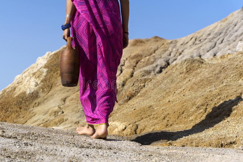 Barefooted woman with a jug. A barefooted woman in ethnical clothes carries in her hand a clay jug stock photos