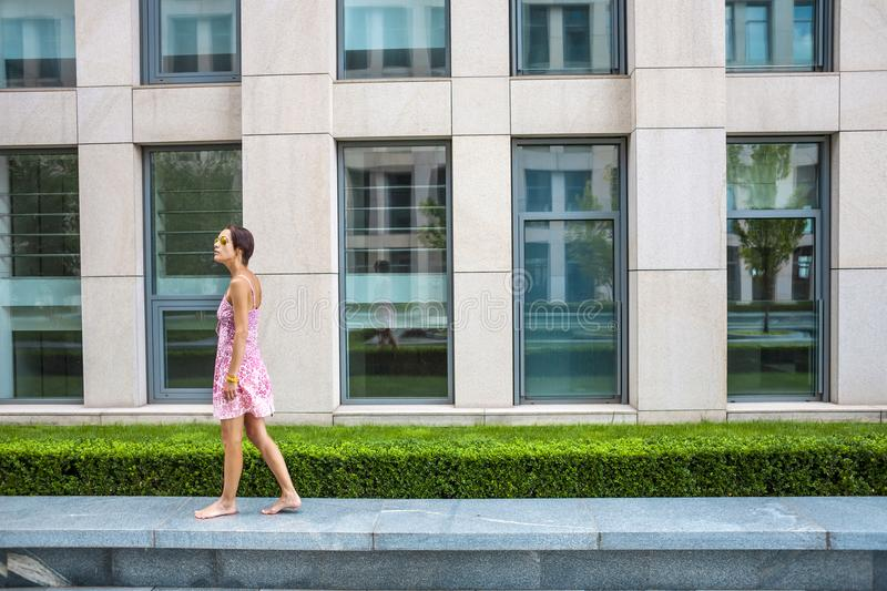 A barefooted woman is walking down the street. royalty free stock photography