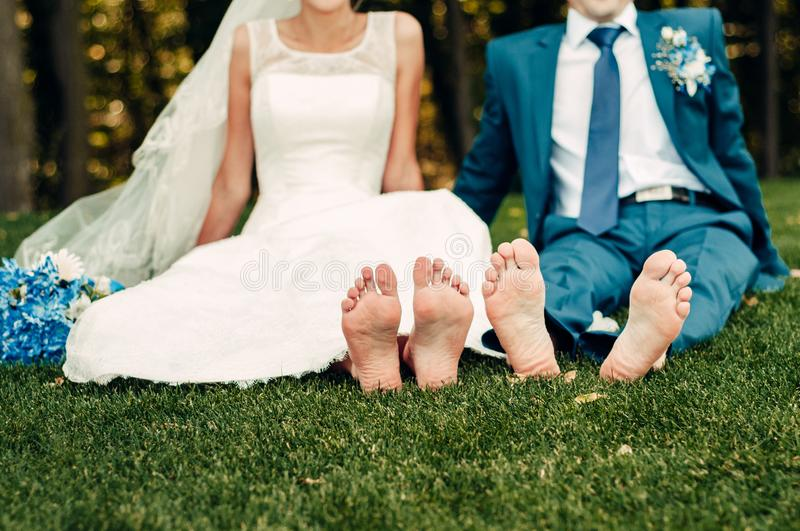 Barefooted young fair-haired bride and her fiance sits on the grass in an exotic park stock images
