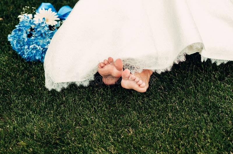 Barefooted young fair-haired bride sits on the grass in an exotic park royalty free stock photography