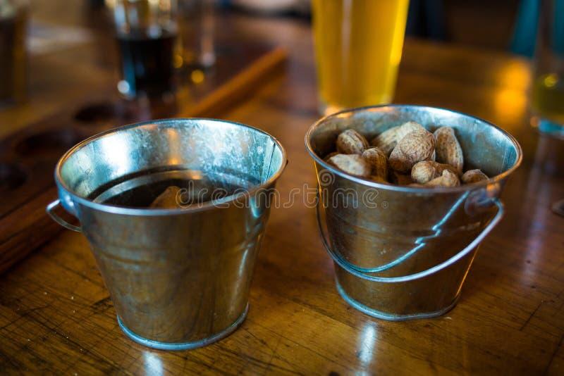 Bareimer mit rohen Erdnüssen und Bier stockfotos