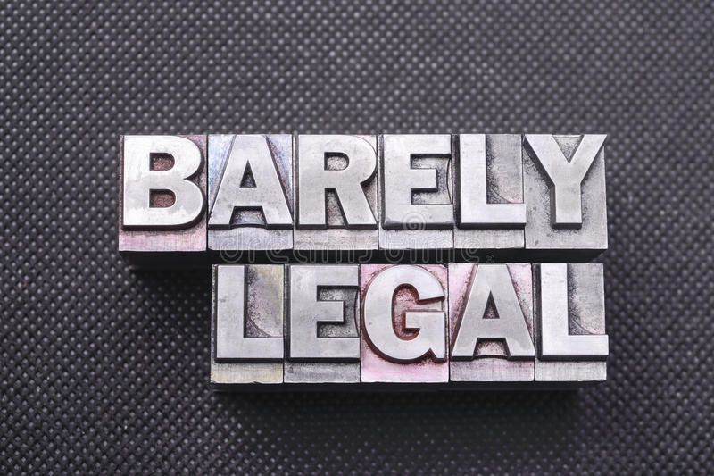Barely legal. Phrase made from metallic letterpress blocks on black perforated surface royalty free stock photos