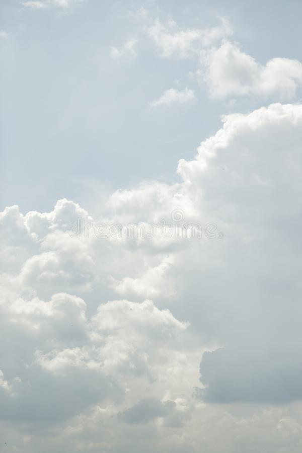 Barely noticeable birds in clouds. Sun rays through the cloud royalty free stock image