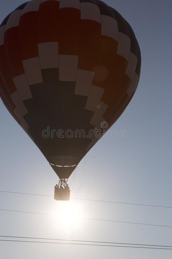 Barely Over the Wire. Near-silhoutte of a hot air balloon barely clearing telephone wires. Dawn sky. Sun misty behind morning clouds royalty free stock photo
