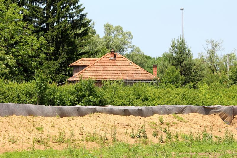 Barely visible family house red roof tiles behind temporary box barriers flood protection covered with dark grey geotextile fabric. Surrounded with dense trees royalty free stock photo