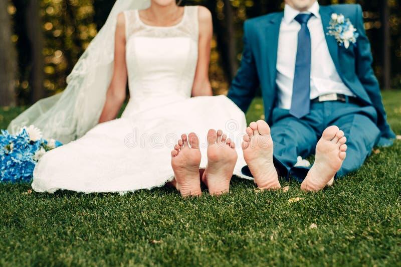 Barfüßig junge blonde Braut und ihr Verlobtes sitzt auf dem Gras in einem exotischen Park stockbilder
