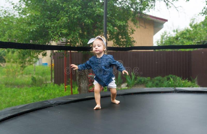 Barfüßig kleines Mädchen mit Bogen genießt, auf Trampoline zu springen lizenzfreies stockfoto
