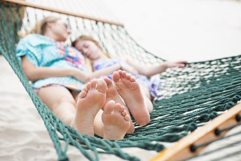 Barfüßig und entspannte Familie, die zusammen in einer Hängematte Nickerchen macht stockfotos