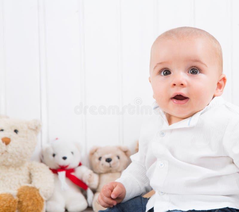 Barfüßigbaby auf weißem Hintergrund mit knuddeligen Spielwaren - nettes kleines stockbilder