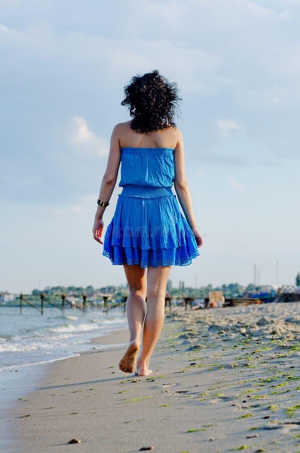 Barfüßigfrau, die auf einen Strand geht stockfotos