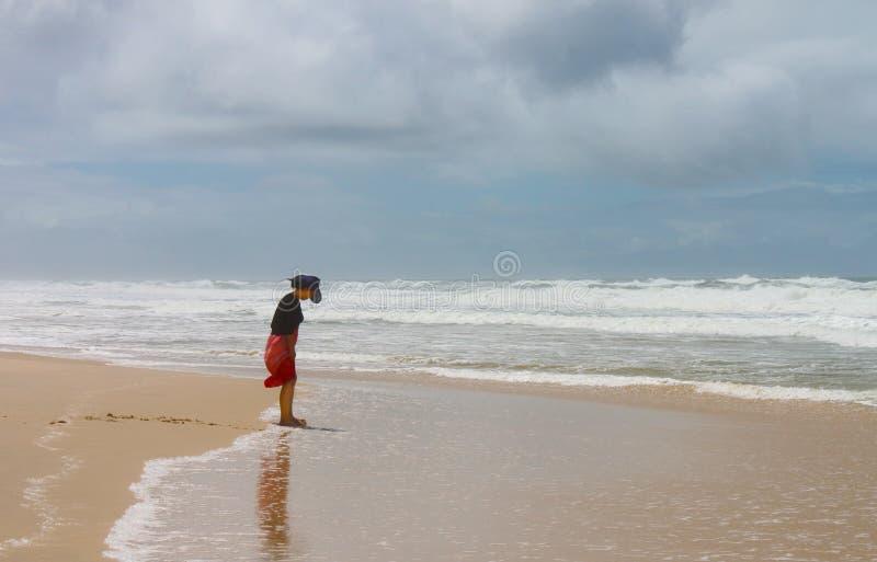 Barfüßigfrau im Hut und im Kleid betrachtet unten ihrem bedeckten Schlamm Füße auf Strand auf dem Gold Coast von Queensland Austr lizenzfreie stockfotos
