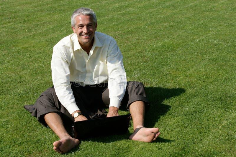 Barfüßiggeschäftsmann, der auf Gras sitzt lizenzfreies stockfoto