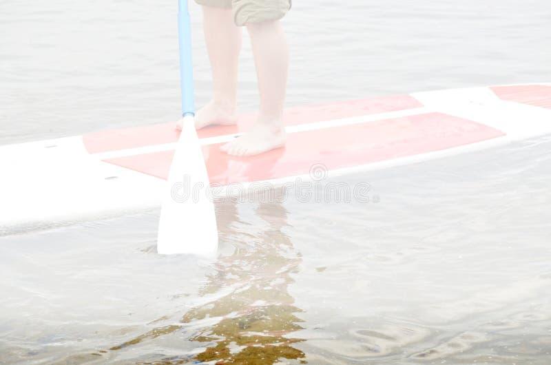Barfüßigmann, der auf Surfbrett mit knielanger Hose der schützenden Farbe steht lizenzfreie stockfotografie