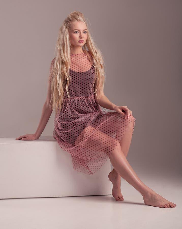 Barfüßigmodell im Kleid, das auf rosa Hintergrund aufwirft stockfoto