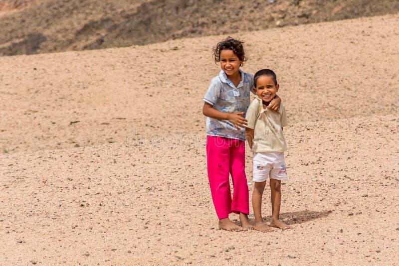 Barfota barn i söndersliten kläder i en beduinby som poserar för foto royaltyfri bild