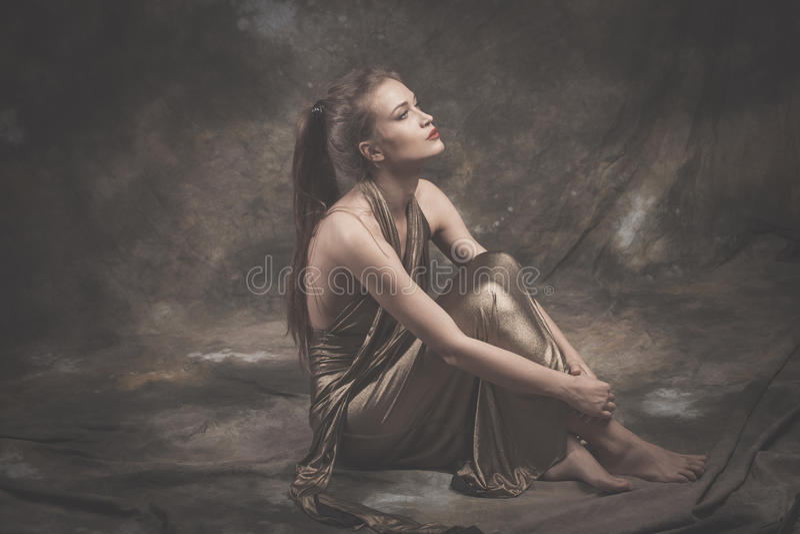 Barfota elegant ung kvinna i guld- klänning arkivfoton