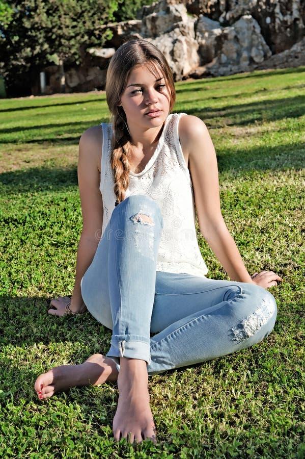 Barfota flicka i riven sönder jeans royaltyfri fotografi