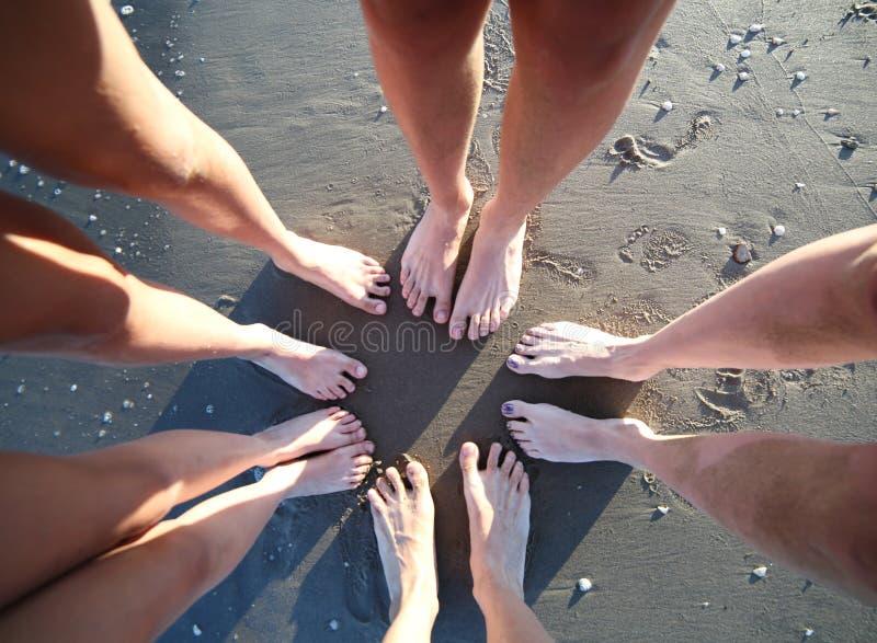 Barfota fot av en familj av fem med ben på den sandiga stranden f royaltyfri fotografi