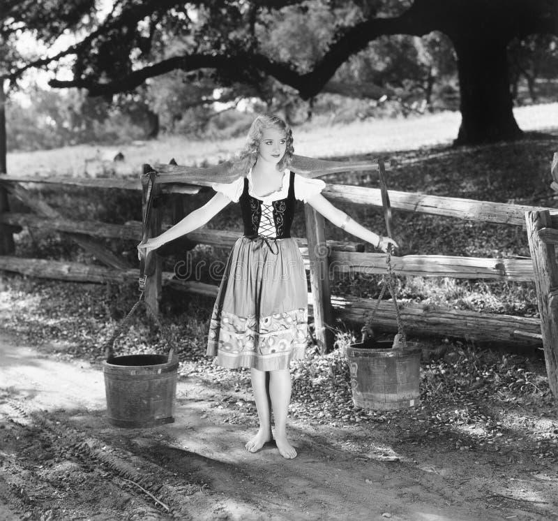 Barfota kvinna i bundna hinkar för ett vatten för klänningslivklänning bärande på skuldrapoler (alla visade personer inte är läng arkivfoton