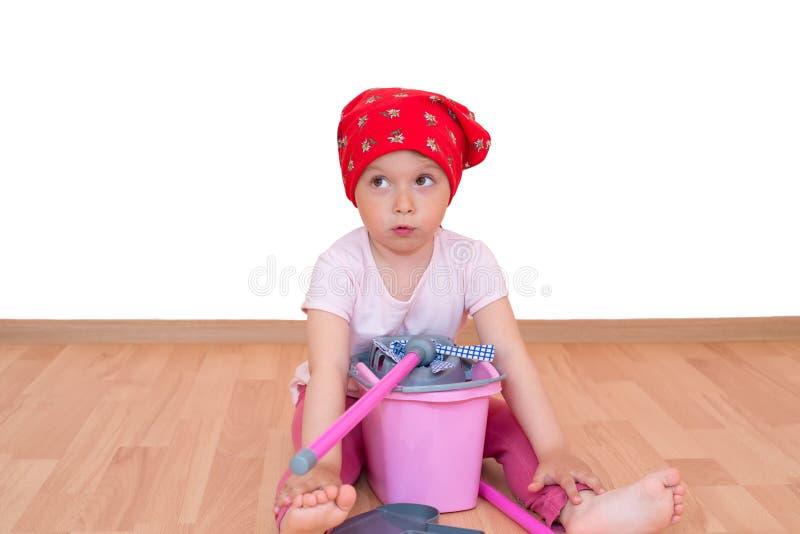 Barfota liten flicka med golvmopp och hink som sitter p? det isolerade golvet fotografering för bildbyråer