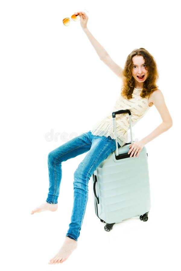 Barfota mager flicka som sitter p? bagage royaltyfria bilder