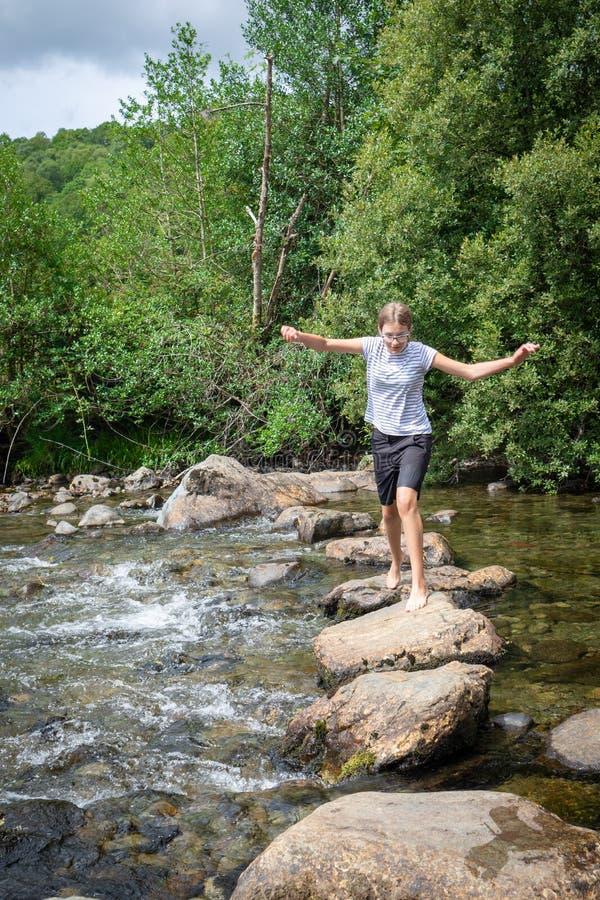Barfota tonårs- flicka som korsar floden Duddon över att kliva royaltyfri foto