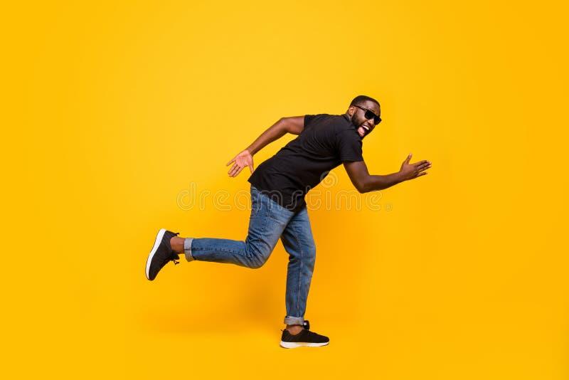 Bargain kommer Bild på sidan med fulllängdsprofil av en svindlande afro american-kille går snabbt och smidigt, otrolig försäljnin royaltyfri foto