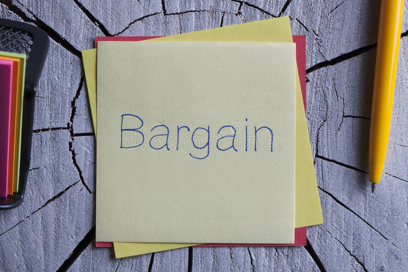 Bargain written on a note. Top view of Bargain written note on the wood chippings board stock images