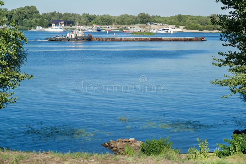 Barge with cargo on river, view from the shore. Sunny summer day stock photo